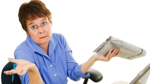 Woman-shurgging-reading-newspaper-Shutterstock